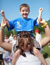 Marcie Smith Harris hold her son Donovan Smith-Lariviere, 6, on her  shoulders while they get