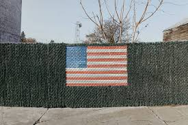 American Flag In A Fence By Brianna Lee Stocksy United