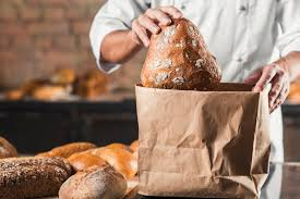 putting baked bread in brown paper bag