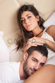 romantic young couple hugging on bed in