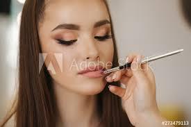 makeup artist applies lipstick hand of