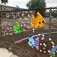 School Kids Creating Design On Chain Link Fences Using Fence Pixels Garden Fence Art Fence Weaving Fence Art