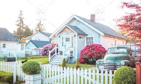 A Classic Suburban House With A White Picket Fence And Old Farm Truck Parked In The Drive Way Stock Photo 5456cdbf 168f 4263 B5b0 4a54498a0da9