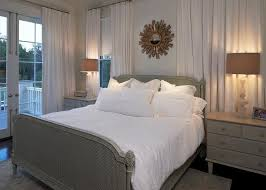 gold sunburst mirror over gray cane bed