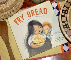 The book cover depicts a mother holding a child who is eating fry bread from the bowl the mother holds in her other hand.