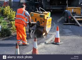 Workmen attending to footpath pavement repairs in residential ...