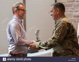 "U.S. Army Garrison Wiesbaden Command Sgt. Maj. Larry Addington presents a  golden microphone plaque to AFN Wiesbaden's radio-show host and emcee of  the ceremony, Paul ""the Brit"" Hughes for his contributions to"