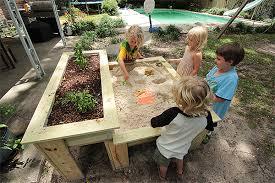 kids sandbox with a raised herb garden