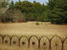 A Wagon Wheel Fance With An Old Red Barn Across The Pasture Karencaseysmith Com Wagon Wheel Decor Wheel Decor Wagon Wheel