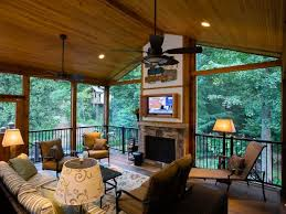 covered porch with a fireplace and tv