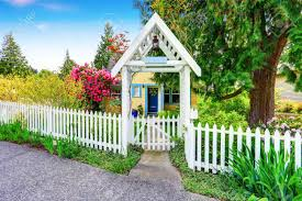 Small Yellow House Exterior With White Picket Fence And Decorative Stock Photo Picture And Royalty Free Image Image 61425700