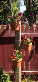 Diy A Seasonal Flower Pole Sink A Fence Post Attach Hangapot Hangers In A Spiral Or Scattered Design Hang Cla Patio Flower Pots Patio Flowers Hanging Plants