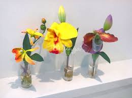 faux orchids in a glass vase favors