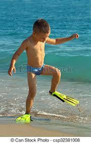 funny kid walking the beach wearing