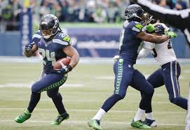 Seattle Seahawks' Marshawn Lynch (24) runs the ball as Kevin Norwood blocks  St. Louis Rams' T.J.