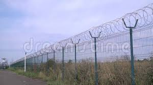 Long Green Steel Fence With Barbed Wire On Top Of It Guard Tower Near It Stock Footage Video Of Metal Prisoner 165224616