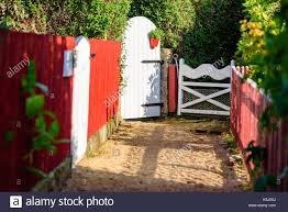 White Garden Gates At The End Of A Gravel Trail Red Picket Fence Stock Photo Alamy