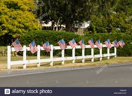Patriotic Display Of American Flags Waving On White Picket Fence Next To A Road Typical Small Town Fourth Of July Independence Day Decorations Stock Photo Alamy