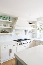 white marble tile backsplash and vent