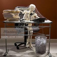 skeleton sitting at desk talking on