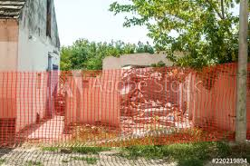 Damaged Broken And Demolished House With Collapsed Roof Surrounded With Orange Safety Net Barrier For Construction Sites Buy This Stock Photo And Explore Similar Images At Adobe Stock Adobe Stock