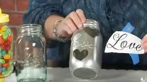 she puts hot glue on a mason jar then