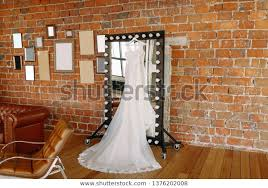 wedding dress hanging on mirror studio