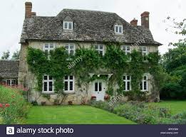 buscot village house three story wisteria ivy stone lawn herbaceous Stock  Photo - Alamy