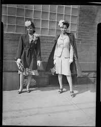 Two women, including Ada Bell on left, the other in suit and coat, with  flowers in hair, standing on sidewalk in front of building with glass block  window | CMOA Collection