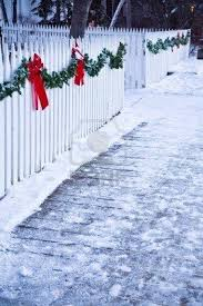Christmas Garland And Red Bows On A White Picket Fence Christmas Garland Holiday Decor Christmas Outdoor Christmas Decorations