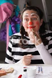 woman putting on clown makeup stock