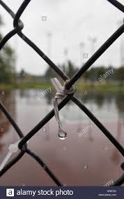 A Small Wire Tie On A Chain Link Fence With A Drop Of Water Stock Photo Alamy