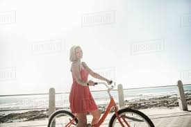 young woman with bicycle on seafront