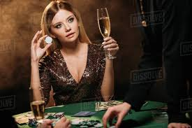 Beautiful woman holding glass of champagne and poker chip at table ...