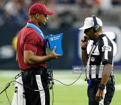 Umpire Adrian Hill reviews a play during a preseason game between ...