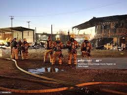 Orange County fire fighters watch as a ...