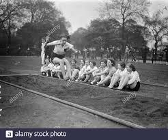 Miles Spencer performing the long jump to a group of observers . 2 ...