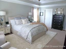 area rug over carpet in bedroom with