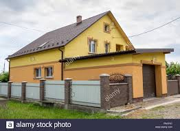 View From The Clean Paved Street Of Detached Garage With Big Automatic Door New Residential Cottage With Balcony Behind Brown Brick Forged Fence Rea Stock Photo Alamy