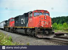 Byron, Wisconsin, USA. Pair of Canadian National diesel locomotives lead a  freight train up a grade On Byron Hill in ...