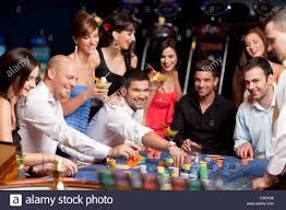 people betting, playing roulette in a night casino Stock Photo ...