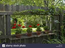 Pass Through To Neighbors Hole In Fence With Shelf For Geranium Stock Photo Alamy