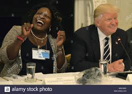 President Donald Trump (R) draws a laugh from Fontana, California Mayor Acquanetta  Warren, as he introduces