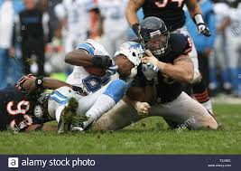Chicago Bears defensive end Adewale Ogunleye (L) and defensive tackle Dusty  Dvoracek (R) tackle Detroit Lions receiver Calvin Johnson for a 6-yard loss  on a reverse during the fourth quarter at Soldier