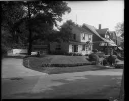 Two Story House With Clapboard Siding Picture Window And Large Tree Next Fence And Attached Garage On Hillside With Bushes And Lamp Post Road In Foreground House With Striped Porch Awning On