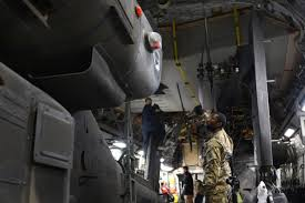 U.S. Army Spc. Byron Holmes, foreground, holds the rear blades of an AF-64  Apache helicopter