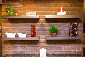 red brick wall with floating shelves in