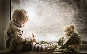 cute boy and teddy bear at window side