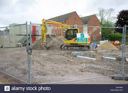 Uk Construction Site With Safety Fencing Sign And Mechanical Digger Stock Photo Alamy