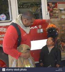 Wesley Collins, a firefighter from Prince George County Fire Department,  places his fire hat on top of his son Jaire during a recent tour Of Fire  Station No. 2 March 26. Collins